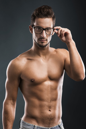 shirtless male: Shirtless male model posing with glasses over a blue background Stock Photo