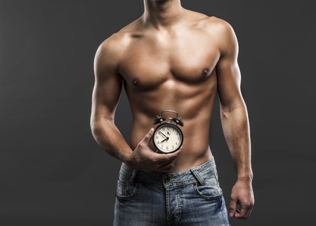 Sexy and handsome young man holding a clock over his belly photo