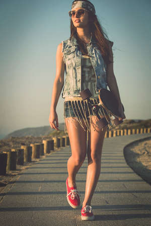 Beautiful Young woman walking and holding a skateboard photo