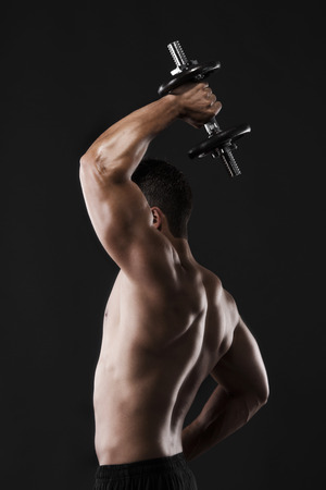 Portrait of a muscular man lifting weights against a dark background photo