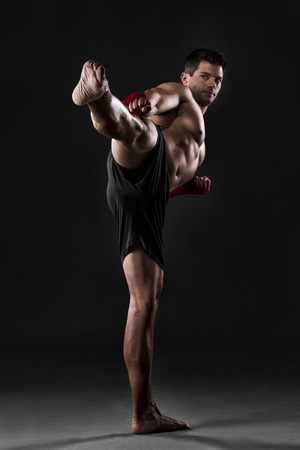 Portrait of a muscular man practicing body combat against a dark background photo