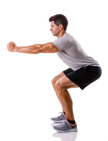squatting: Hombre atl�tico correr haciendo sentadillas, aisladas sobre un fondo blanco
