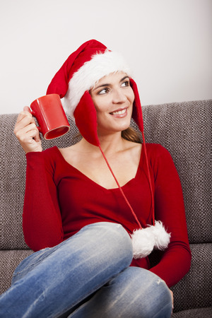 Beautiful woman sitting in the sofa and wearing a santa hat photo