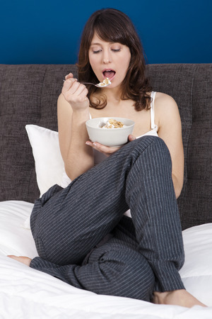 Beautiful and healthy young woman eating a cup of cereals with yogurt photo