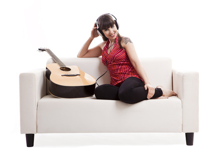 Beautiful woman sitting on the sofa with her guitar and listen music, isolated on white photo