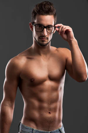 Shirtless male model posing with glasses over a gray background photo