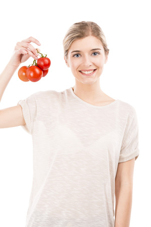 Beautiful girl smiling and holding red tomatoes in the hands, isolated over a white background photo