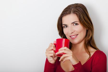 mujer tomando cafe: Joven y bella mujer bebiendo un café caliente, contra una pared gris Foto de archivo
