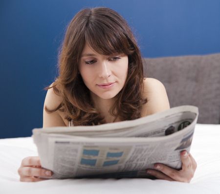 Beautiful young girl lying on the bed and reading the newspaper photo