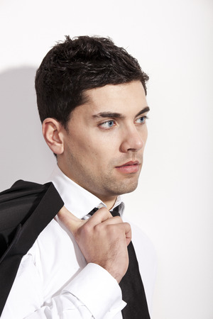 Studio portrait of a young businessman holding is jacket photo