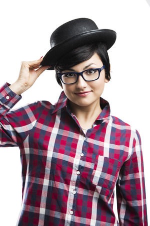 Beautiful girl with a funny face wearing a hat and nerd glasses, isolated over white background photo