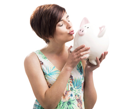 Beautiful happy woman kiising a piggy bank, isolated over a white background photo