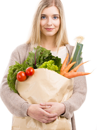 Beautiful blonde woman carrying a bag full of vegetables, isolated over white background photo