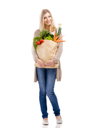 Beautiful blonde woman carrying a bag full of vegetables with thumbs up, isolated over white background photo