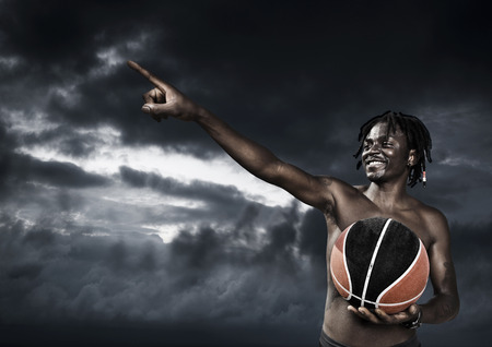 Portrait of young man street basket player against a dark sky photo