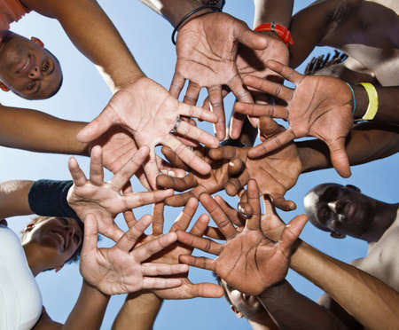 african lady: A group of mixed race people putting hands together