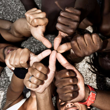 A group of mixed race people with hands doing thumbs up photo