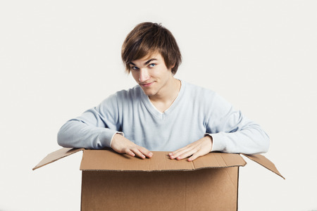 Portrait of a handsome young man inside a cardbox photo