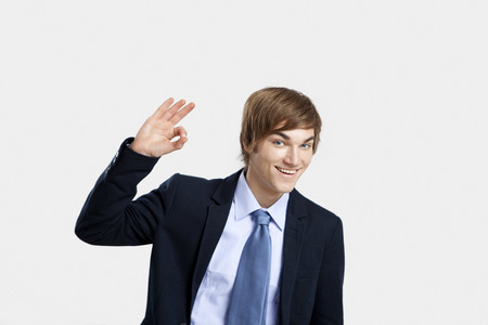 Young businessman doing a Okay signal to the camera, over a gray background photo