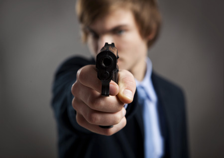 Stressed businessman holding and pointing a gun to the camera photo