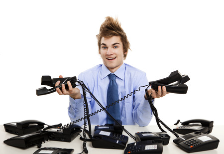 Young man sitting in the office and answering several phones at the same time Stock Photo