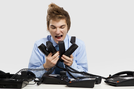 Young man holding and yelling to the phones photo