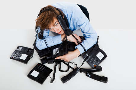 answering call: Exhausted man sitting with a bunch of phones over him