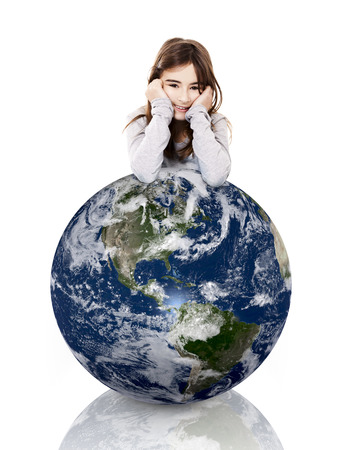 Little girl resting with her arms over a small planet earth, isolated on white background photo