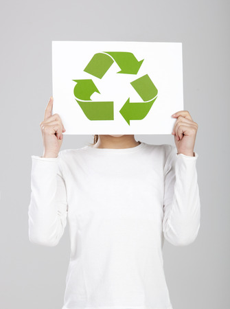 Child holding a paper with the recycle symbol on it, isolated over a white background photo