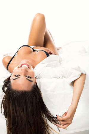 Beautiful and sexy woman lying on the bed and smiling, isolated on white background photo