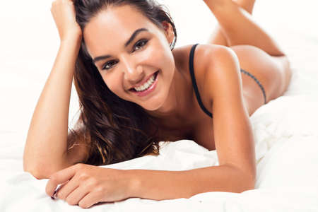 Beautiful and sexy woman lying on bed and smiling, isolated on white background photo