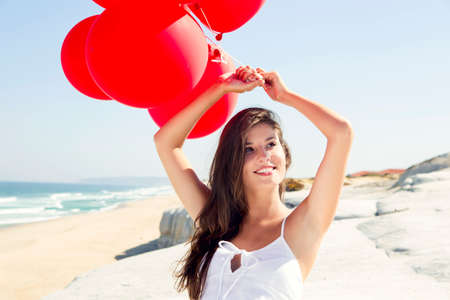 ballons: Beautiful girl with red ballons sitting in the beach  Stock Photo
