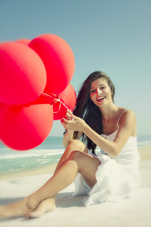Beautiful girl with red ballons sitting in the beach and laughing photo