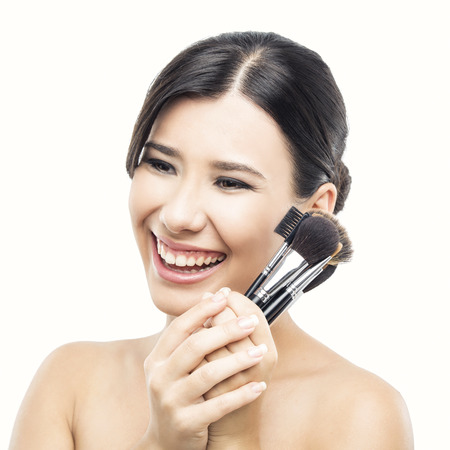 Beauty portrait of an Asian young woman holding make-up brushes photo