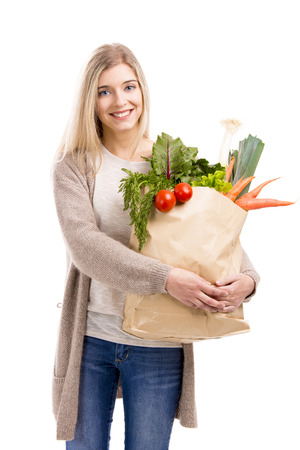 Beautiful blonde woman smiling and carrying a bag full of vegetables, isolated over white background photo