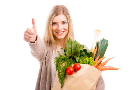 Beautiful blonde woman carrying a bag full of vegetables with thumbs up, isolated over white background Stock Photo
