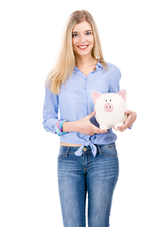 Beautiful and attractive blonde woman holding a piggy bank, isolated over white background photo