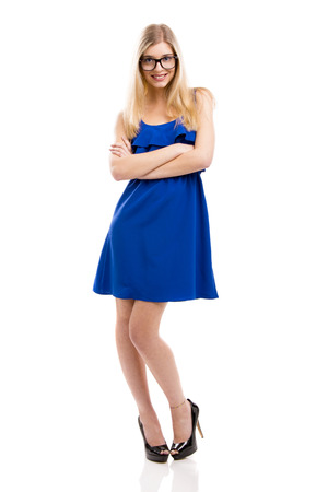 Beautiful fashion woman in blue dress using nerd glasses, isolated over white background photo