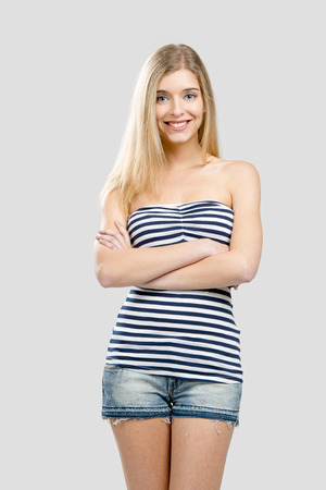 Beautiful young woman smiling and standing over a gray background photo