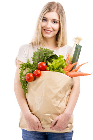 Beautiful blonde woman carrying a bag full of vegetables with thumbs up, isolated over white background Stock Photo - 24772449