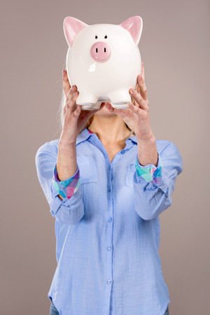 Beautiful and attractive blonde woman holding a piggy bank in front of her head