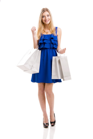 Beautiful woman in a blue dress with shopping bags, isolated on a white background photo