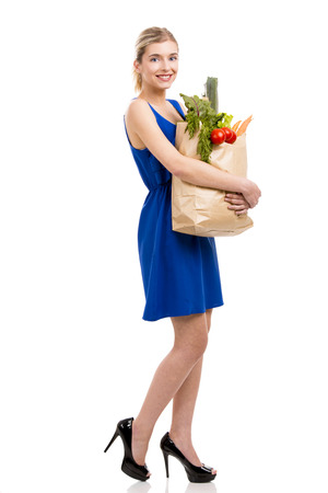 Beautiful and attractive woman carrying a bag full of vegetables, isolated over white background photo