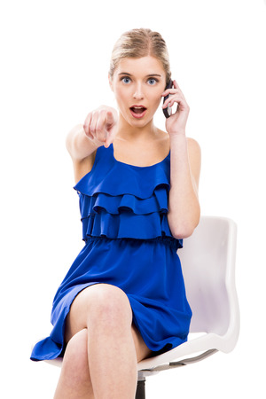 Beautiful woman sitting on a chair talking at phone, isolated over white background photo