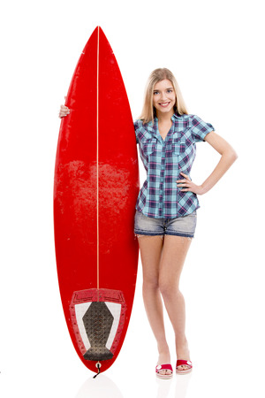 Beautiful young woman with a surfboard, over a gray background photo