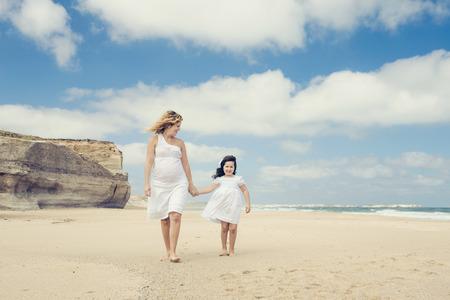 mujer hijos: Hermosa mujer embarazada y su pequeña hija caminando en la playa Foto de archivo