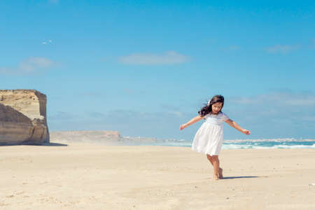Little girl dancing on the beach with a white dress photo