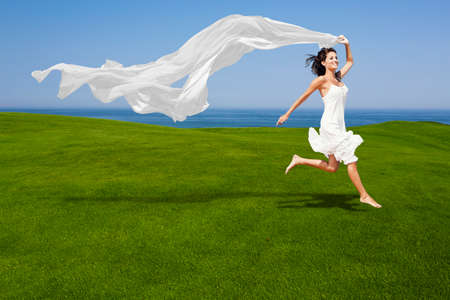 Beautiful woman running and jumping on a green meadow with a white tisue photo