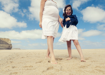Beautiful pregnant woman and her little daughter on the beach photo