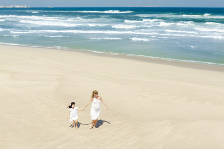 Beautiful woman and her little daughter walking on the beach photo